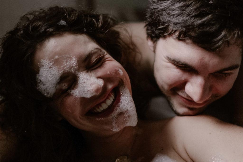 Couple de futurs parents jouant dans un bain moussant